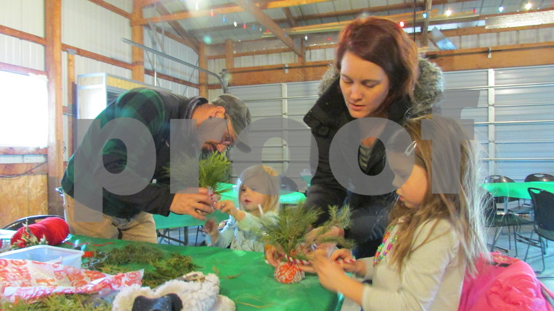 Jacob Wyatt of Sycamore helps his daughter, Rowan, 2, while Geri Wyatt helps her daughter, Ezra, 5, make holiday ornaments Saturday during the Holiday Open House at the Sycamore History Museum.