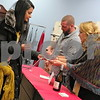 Taste of the Holidays volunteer Ben Brooks (center) pours wine while Kay Smith (right) marks off NIU graduate student Garima Lohani's wine-tasting card at Blu Door Decor, 209 E. Lincoln Highway, during the event Saturday in downtown DeKalb.