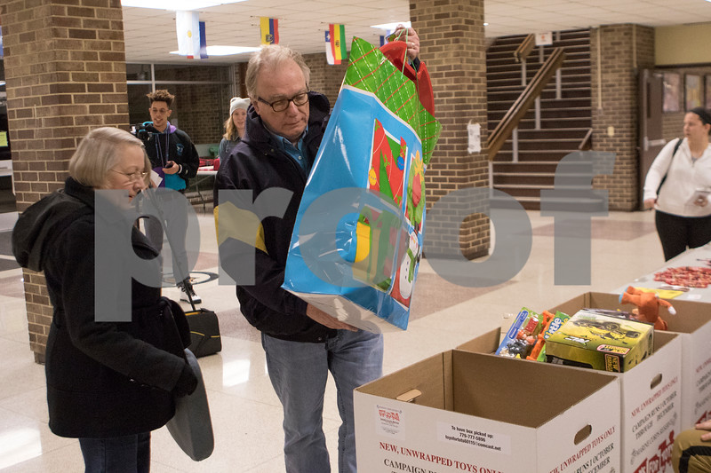 Sam Buckner for Shaw Media.<br /> Rosemary and Bernie Boona drop off a big bag of toys for the Guns and Hoses VS. District 428 staff fundraiser game for Toys for Tots on Monday December 4, 2017.