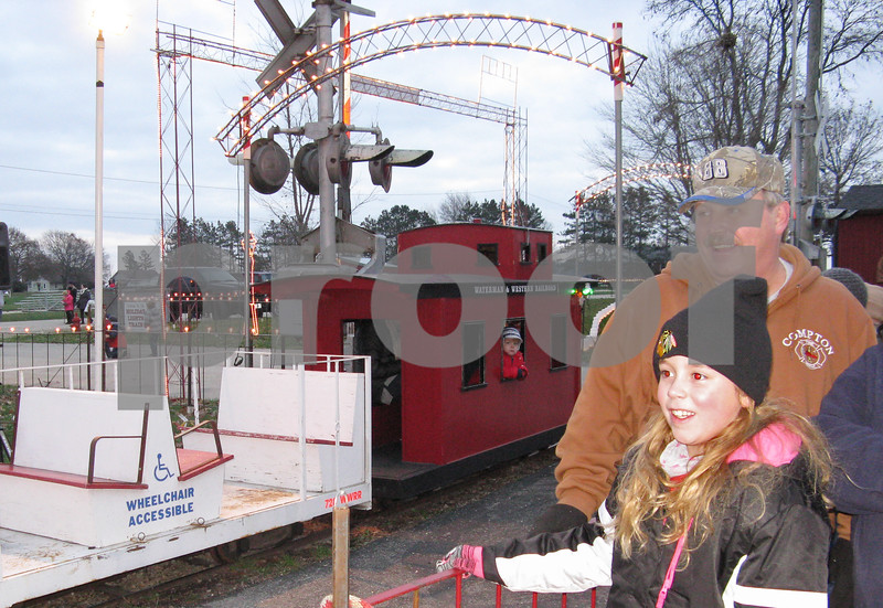 Aimee Barrows – news@daily-chronicle.com<br /> Kylie Kofoid, 9, and her grandfather, Steve Kofoid, wait to board the holiday lights train Saturday in Waterman.