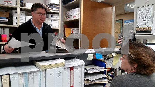 David Simpson, 48, a Democrat from Shabbona, files his petition to run for committeeman in his Shabbona's 1st Precinct on Monday morning with Lynne Kunde, DeKalb County's election judge coordinator, at the Legislative Center.