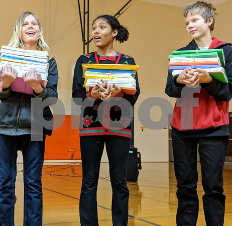 Clinton Rosette eighth-graders Ian Hanson (left) Olivia Yarborough and James Myroth-Erlandson held up the drafts author Shelley Pearsall went through to complete three of her novels. Pearsall wanted to demonstrate what the writing process is.