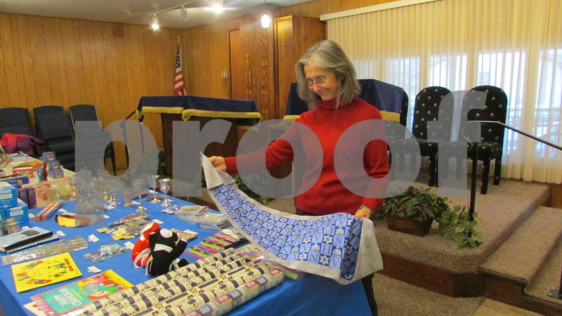 Congregation member Liz Blau looks at a table runner at the Hannukah Shop.