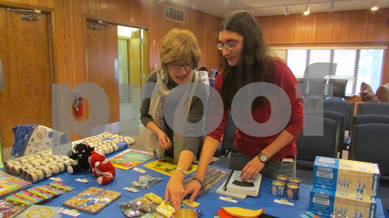 Jackie Gorman (left), a member of Congregation Beth Shalom who runs the gift shop, sorts items with her daughter, Caitlin.