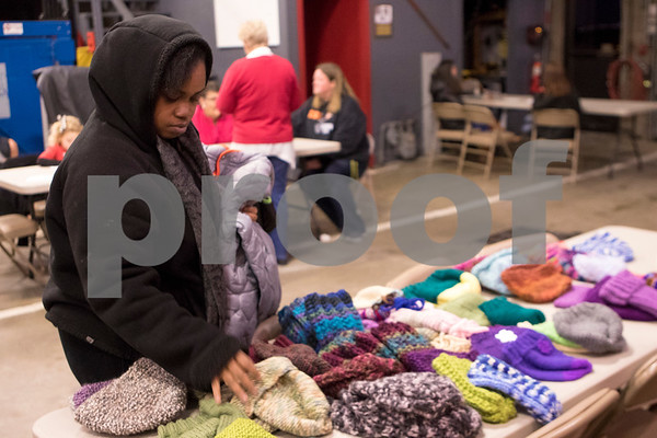 Sam Buckner for Shaw Media.<br /> Angela Harris-Horton picks out hats for her kids at the 3rd annual Operation Warm Coat giveaway on Wednesday December 14, 2016.