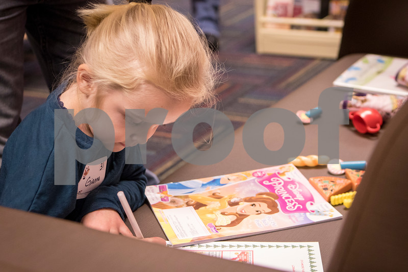 Sam Buckner for Shaw Media.<br /> Gianna Romano (5) completes part of her scavenger hunt at the Sycamore Public Library holiday open house on Wednesday December 14, 2016.