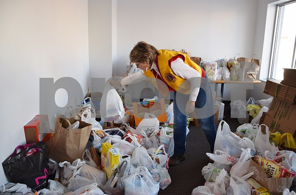 Franklin Mall Christmas Food Project grocery box chairwoman Karen Spangler adds a bag of donations to a pile at the Sandwich Fire Department. Food donations are needed to help fill food boxes that will be delivered on Christmas Eve to more than 240 families in the Sandwich community. The food project needs approximately four tons of food to fill the boxes.