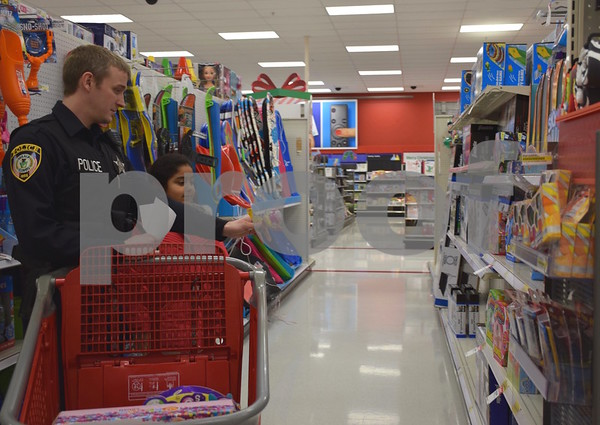 Detective Sonny Streit helps 8-year-old Desiree Barrios shop during the Heroes and Helpers event Sunday at Target in DeKalb.