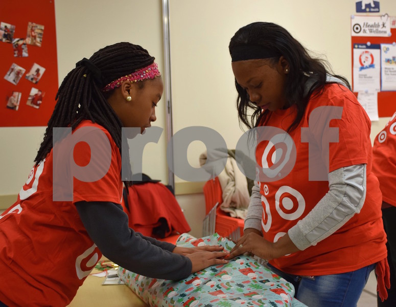 Robin Gibson (right) and her 11-year-old daughter, Sydni, both of DeKalb, were two of more than 30 volunteers who helped wrap gifts during the Heroes and Helpers event Sunday at Target in DeKalb.