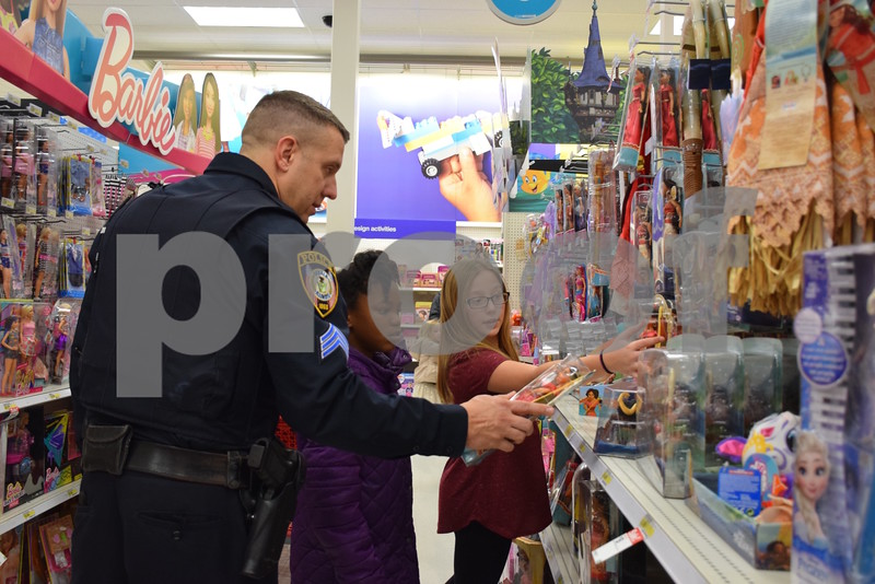 DeKalb Police Sgt. Tony Kwasniewski and his 11-year-old daughter, Kayla (right), help 9-year-old Tyjaya Frierson shop during the Heroes and Helpers event Sunday at Target, 2555 Sycamore Road, DeKalb. Thirteen DeKalb police officers volunteered to help with the event, which provided 38 children in DeKalb School District 428 the opportunity to choose and take home more than $100 in Christmas presents.