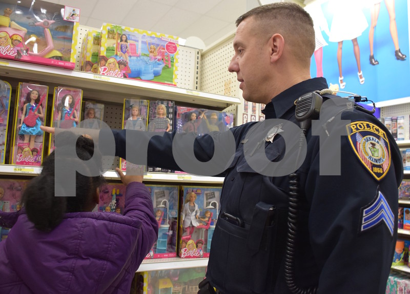 DeKalb Police Sgt. Tony Kwasniewski helps 9-year-old Tyjaya Frierson shop during the Heroes and Helpers event Sunday at Target in DeKalb.