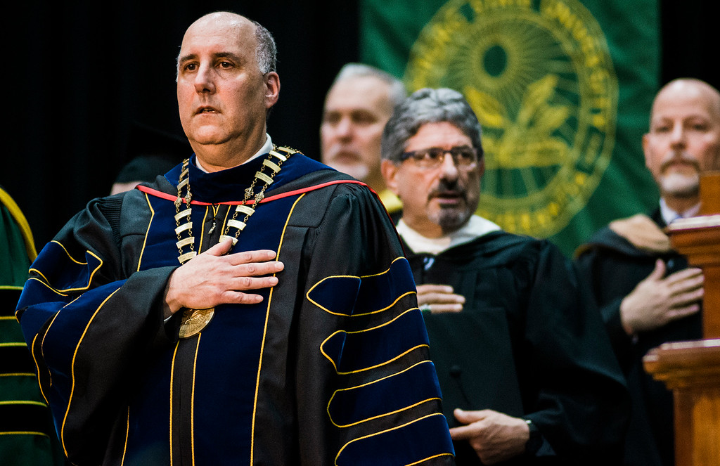 . President Richard Lapidus and Fitchburg Mayor Stephen DiNatale stand for the National Anthem during the 121st Annual Graduate Commencement at Fitchburg State University on Thursday, May 18, 2017. SENTINEL & ENTERPRISE / Ashley Green