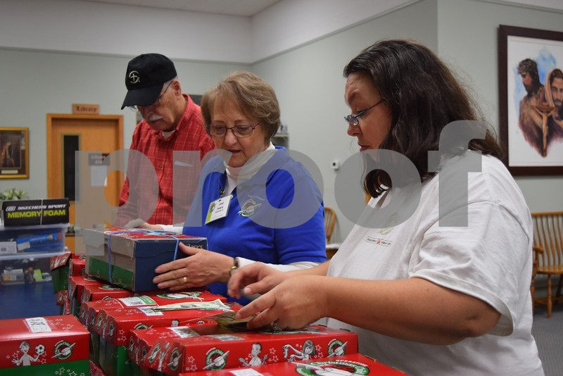 Volunteers with Operation Christmas Child organize donated shoeboxes full of gifts for children around the world at First Baptist Church, 530 W. State St. in Sycamore, on Nov. 18. This year, the church collected 1,638 shoeboxes from the community.