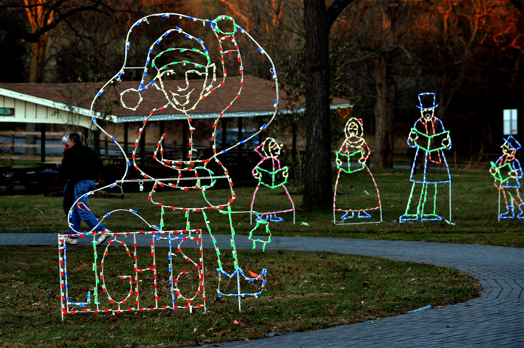 . (Bob Raines-/Digital First Media)  A couple takes a walk past lighted figures of an elf and some carolers in Fischer\'s Park, Towamencin Wednesday, Dec. 20, 2017.