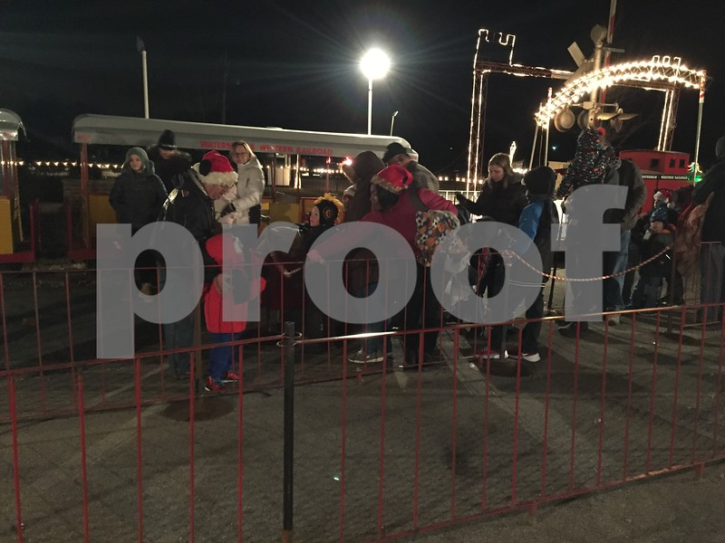 Residents line up to board the Holiday Lights Train on Saturday in Waterman.