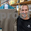 Eric Armstrong, general manager at Greenacre Cleaners in DeKalb, poses with recent suit donations Dec. 22 at the facility. Greenacre and Suits for Success work together to collect, clean and distribute suits for new parolees who attend job interviews when they get out of Illinois prisons.