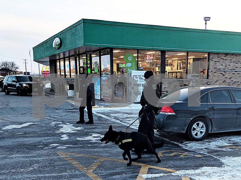 Genoa Police Chief Robert Smith (center) and Kane, a Genoa police dog, search for a suspect in an armed robbery that occurred at the BP gas station, 1615 DeKalb Ave. in Sycamore on Wednesday, Dec. 27, 2017. The dog caught a scent but was not able to locate the perpetrator.