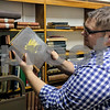 Sycamore Library Director Jesse Butz displays some of the older books and reference volumes the library keeps Wednesday. The library has a collection of some of the first books it had when it opened, along with the logs and notes of its running during the early years of the library.