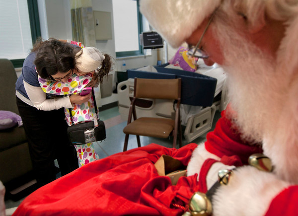8 year old Hannah Matlaga gets a present form Santa. Santa Claus visited the Pediatrics department of Holy Name Medical Center in Teaneck to give presents to the children just days before Christmas.<br /> Photo by Jeff Rhode / Holy Name Medical Center 12/18/13
