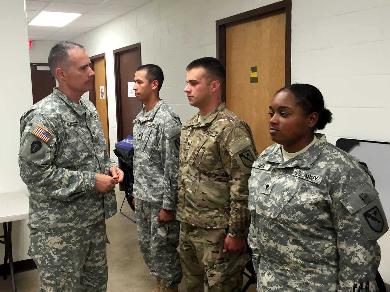 Col. Scott Mac Leod, commander of Joint Task Force 136 (Maneuver Enhancement Brigade), presents his commander's coin to members of the 136th Expeditionary Signal Battalion during his visit to their mobilization training site in North Fort Hood August 27, 2015. Photo by 1st Lt. Jared Reinhardt.