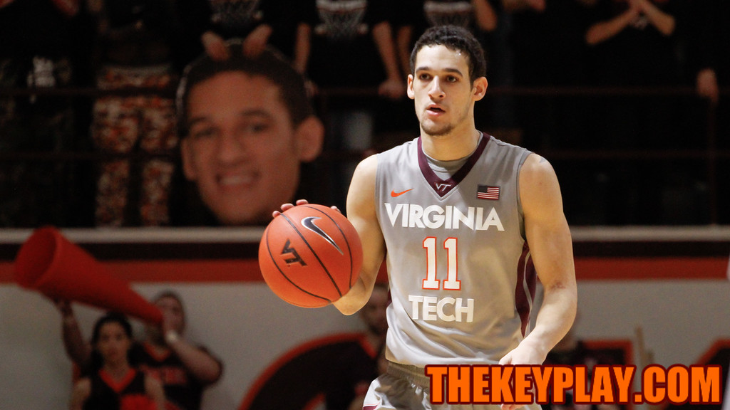 Devin Wilson dribbles the ball up the court as the Cassell Guard show off a giant poster of his face in the student section. (Mark Umansky/TheKeyPlay.com