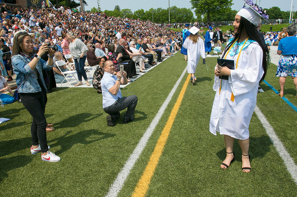 . The 149th graduation exercise for Leominster High School was held on Saturday, June 1, 2019 at Doyle Field. Graduate Phetemany Simmalavong stops for a moment so friend Pim Phetsang and her dad Andrew Mauro, kneeling, could snaps some pictures of her after she got her diploma. SENTINEL & ENTERPRISE/JOHN LOVE