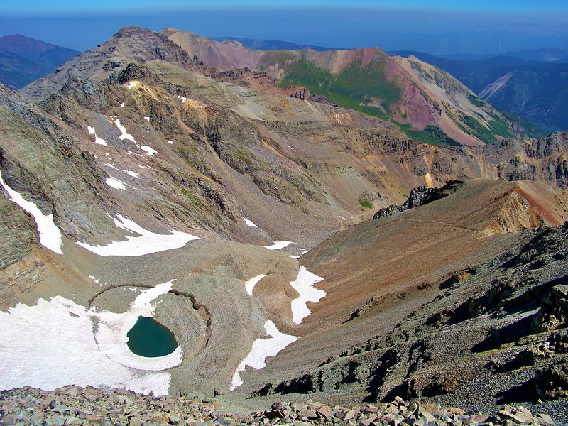 Unnamed peak (13,800 ft.) north of the Castle Peak summit; the sink hole in the basin below dropped 30 feet just weeks before this photo.