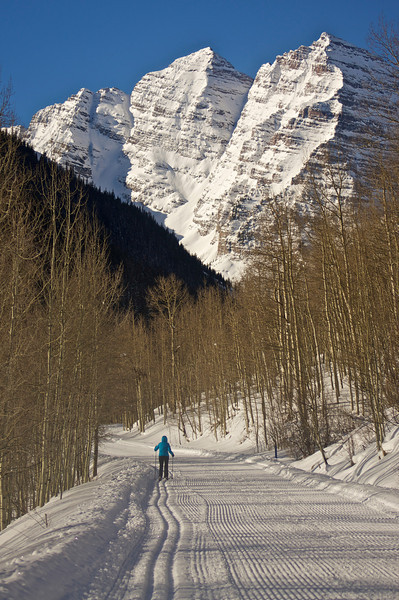The frozen Maroon Bells tower over the snow-packed Maroon Creek Rd., passable in the winter only by skis, snowshoes and snowmobiles; Colorado Elk Range.