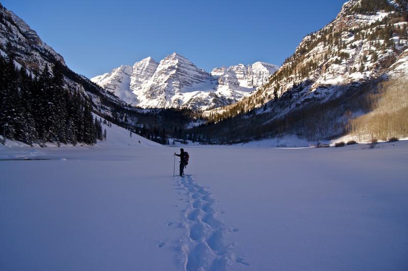 Snowshoeing across frozen Maroon Lake; Colorado Elk Range.