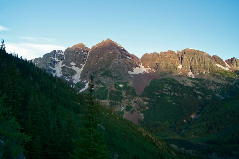 First sunlight on The Maroon Bells, viewed from Pyramid Peak's lower trail; Colorado Elk Range.