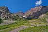 The Maroon Peaks' eastern cliffs appear menacing above the trail beyond Crater Lake; Colorado Elk Range.