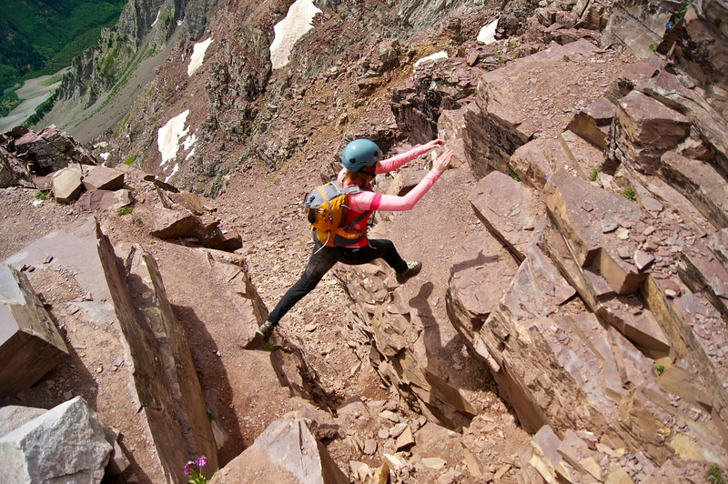 """One of the most notable features of the Pyramid Peak route, the """"leap of faith"""" over an exposed crevasse.  Colorado Elk Range."""