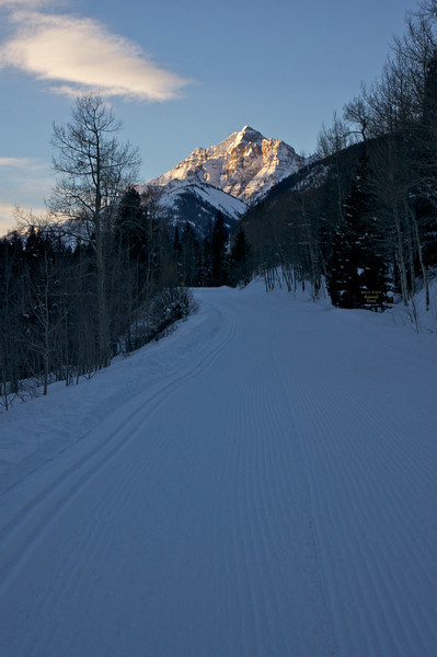 The early morning sun illuminates Pyramid Peak's northeast face; viewed from Maroon Creek Road, accessible in winter only by ski, snowshoe or snowmobile; Colorado Elk Range.