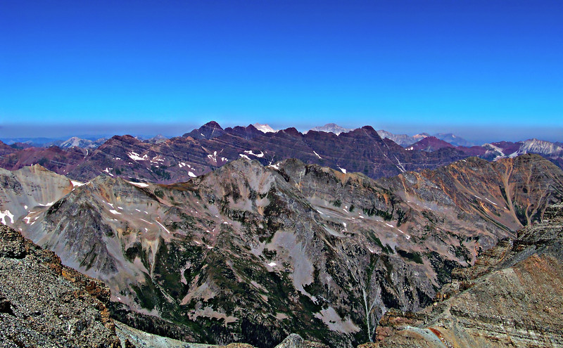 The vast, colorful landscape of the Colorado Elk mountains from the Castle Peak summit; Pyramid Peak, Maroon Bells, Capitol Peak and Snowmass Mountain.