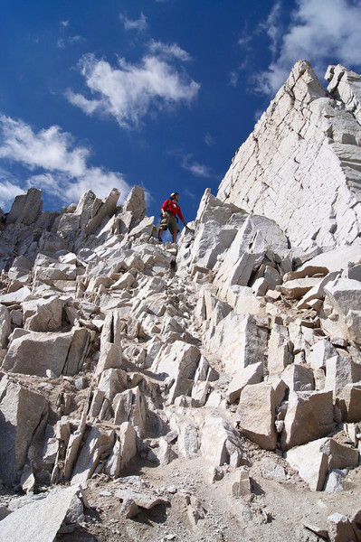 """A climber stands at the top of the """"notch"""" to the upper south ridge of Snowmass Mountain; Colorado Elk Range"""