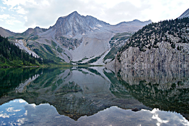 Snowmass Peak and Snowmass Mountain cast an evening reflection on the still lake; Colorado Elk Range