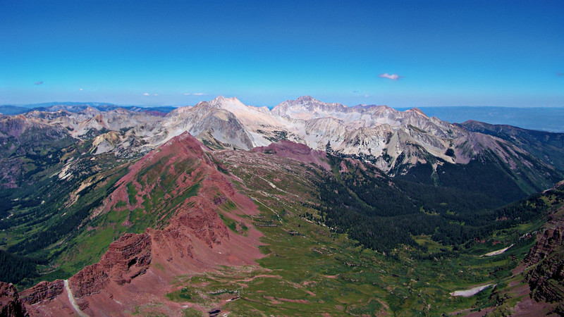 Snowmass Mountain and Capitol Peak rise in stark contrast to the colorful western Elk Mountains