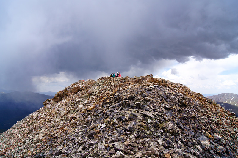 Hikers nervously eye an approaching storm at the summit of Quandary Peak; Colorado Tenmile Range.