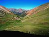 Shadows of hikers on a ridgeline above Silver Creek; in the distance is Handies Peak (14,048 ft.), Colorado San Juan Range.