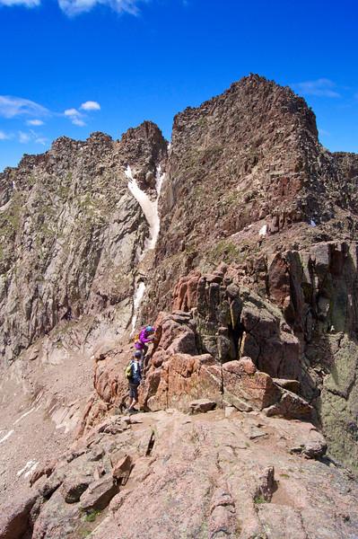 Hikers carefully cross a difficult portion of the Catwalk along the northeast ridge of Mount Eolus; Colorado San Juan Range