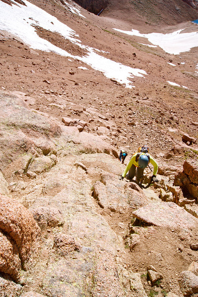 """A look down at hikers ascending the """"green gulley"""" en route to the northeast ridge of Mount Eolus; Colorado San Juan Range"""