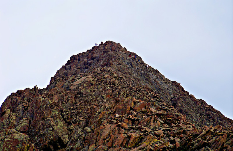 Hikers traverse below the summit of Mt. Sneffels, Colorado San Juan Range.