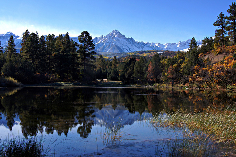 Mount Sneffels in autumn reflects off a pond along Dallas Creek, Colorado San Juan Mountains.