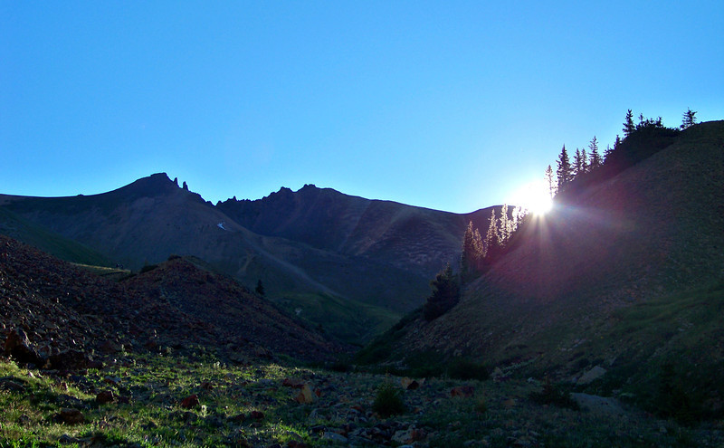 Morning sun peeks into the Silver Creek valley along the trail to Redcloud and Sunshine Peaks, Colorado San Juan Range.