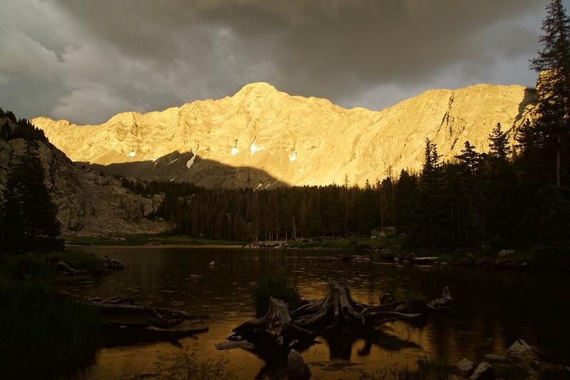 Evening alpenglow illuminates the north face of Little Bear Peak as rain falls on Lake Como; Colorado Sangre de Cristo Range