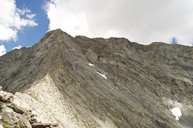 """Looking across the south face of Little Bear Peak.  The """"hourglass"""" gully and upper section of the route lie just above the snow fields in the center of the photo."""