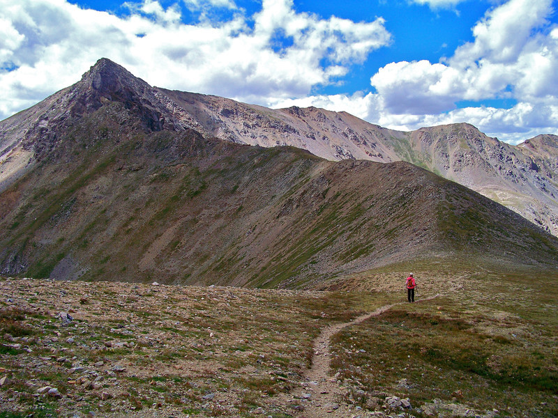 A hiker at the crest of Elkhead Pass below the east ridge of Missouri Mountain