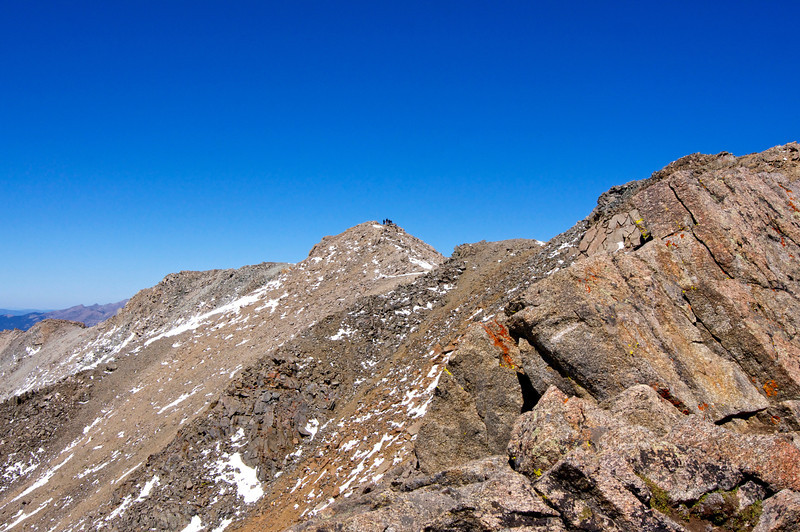 A group of hikers on Mount Massive's true summit; viewed from the false summit to the south; Colorado Sawatch Range.