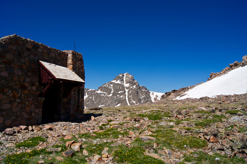 A welcoming stone hut stands near the summit of Notch Mountain as Mount of the Holy Cross comes into view; Colorado Sawatch Range.