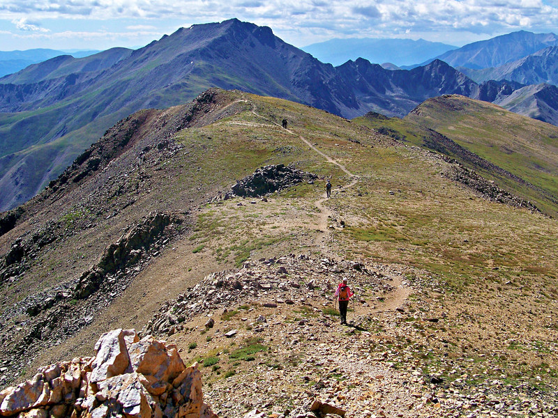 Leaving the summit of Mt. Belford, hikers are treated to clear views of Mt. Harvard and Mt. Yale.